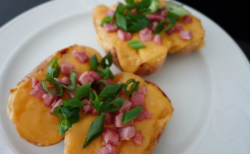 Baked potatoes with cheese, bacon and spring onions